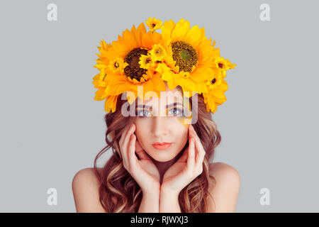 Beautiful young woman wearing floral headband isolated on gray background. Yellow sunflowers wreath of flowers on head looking at you smiling slightly - Stock Photo