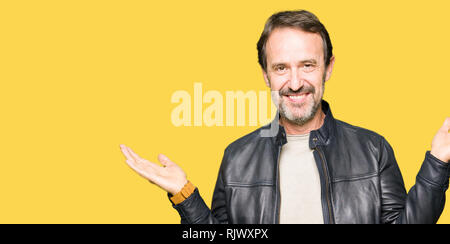 Middle age handsome man wearing black leather jacket Smiling showing both hands open palms, presenting and advertising comparison and balance - Stock Photo