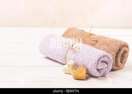 Clean soft towels are tied with natural rope and folded in a row against the background. Selective focus. - Stock Photo