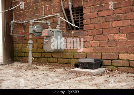 Large black rat trap box or mouse trap box next to a gas meter in a city or urban alley way in Montgomery Alabama, USA.