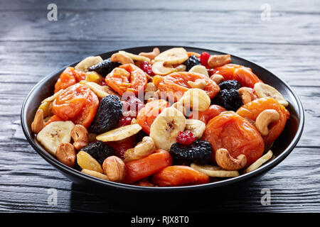 close-up of dried organic Fruits and Nut Mix - banana slices, apricots, raisins, prunes, cherries and cashew on a black plate on a wooden table, healt - Stock Photo