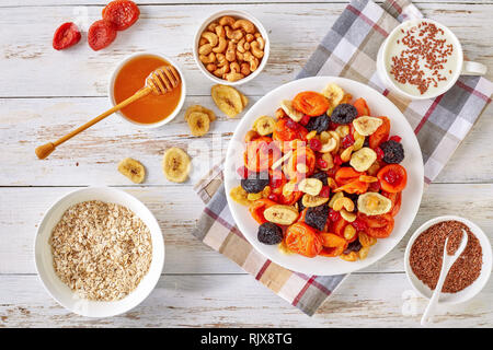 dried Fruits and Nut Mix bowl - banana slices, apricots, raisins, prunes, cherries and cashew on a rustic table with porridge, honey in a bowl and yog - Stock Photo