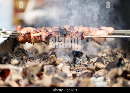 Close up marinated beef kebab. Shashlik preparing on barbecue grill over hot charcoal outdoors - Stock Photo