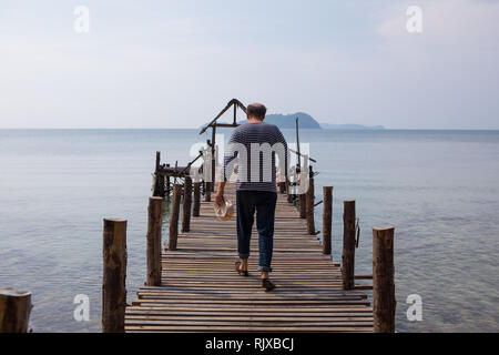 The old man walks on the pier by the sea - Stock Photo