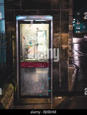 An old run down vandalised public telephone box lit up in the night on the corner of the street in Edinburgh, Scotland - Stock Photo
