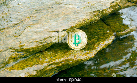 The gold coin of  Bitcoin lies in the rock with sea waves. Bitcoin is a modern way of exchange this crypto currency is a convenient means of payment i - Stock Photo