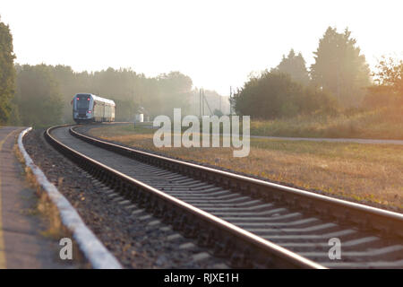 Train leaving the station on foggy morning. Industrial landscape with railway station, colorful blue sky, trees and green grass, yellow sunlight in su - Stock Photo