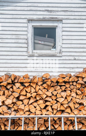 A pile of split logs stacked beside a house in Newfoundland ready for the winter. - Stock Photo