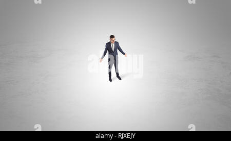Young businessman standing alone in the middle of an empty space  - Stock Photo