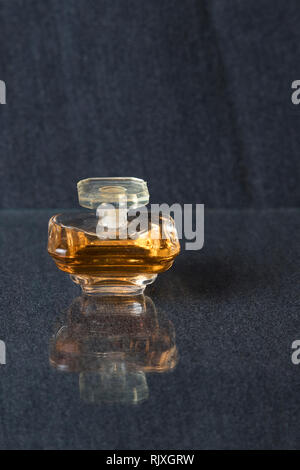 Female perfume in glass bottle on a blue background. - Stock Photo