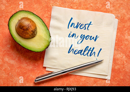 invest in your health - handwiring on napkin with a cut avocado against bark paper - Stock Photo