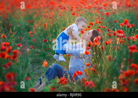 Outdoor portrait. Young mother and her daughter enjoy life time together on a poppy field . Concept of love and happy family. Poppy meadow. - Stock Photo