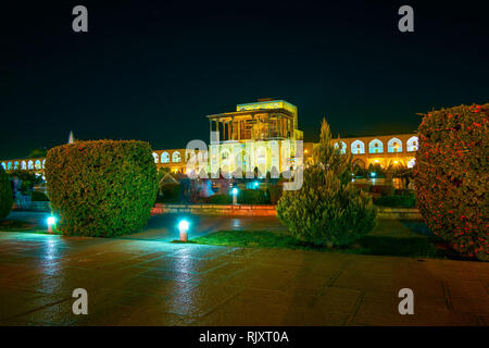 The pleasant evening in Nashq-e Jahad Square with beautifully illuminated Ali Qapu Palace, Isfahan, Iran - Stock Photo