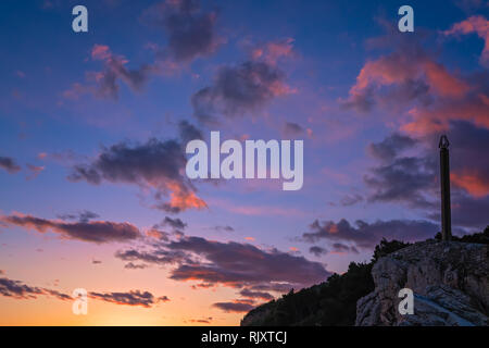 Statue obelisk and Montenegrin flag fluttering in the wind in the fortress on top of cliffs in Petrovac coast at dusk, Montenegro - Stock Photo