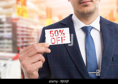 Man presenting white card with fifty per-cent off concept as advertising discount - Stock Photo