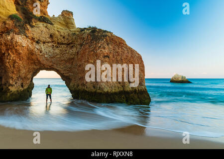 Man standing underneath natural arch of cliff, looking at view of sea, Alvor, Algarve, Portugal, Europe - Stock Photo