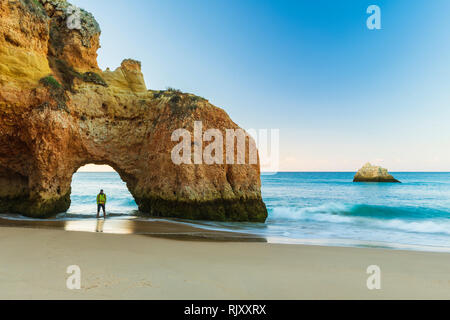 Distant view of man looking at sea view from beach, Alvor, Algarve, Portugal, Europe - Stock Photo