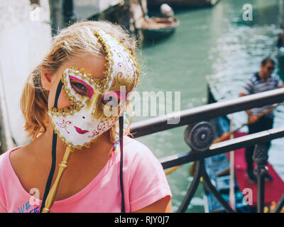 LIttle girl with blue eyes and carnival mask. Carnival in Venice, Italy. - Stock Photo