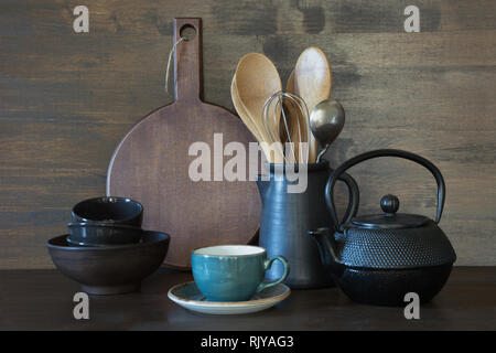 Crockery, clayware, dark utensils and other different stuff on wooden tabletop. Kitchen still life as background. - Stock Photo