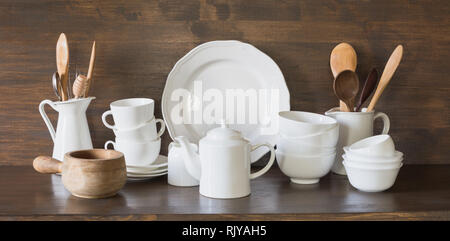 Crockery, clayware, white utensils and other different stuff on wooden tabletop. Kitchen still life. - Stock Photo