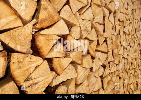 Background image of stacked, dry chopped logs used for firewood. Pile of logs ready to be used in fireplace. Alternative warming method. Natural energ - Stock Photo