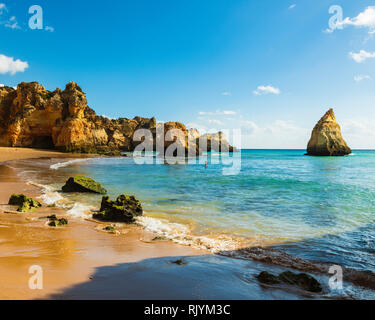 Distant view of large sea stacks in blue sea, Alvor, Algarve, Portugal, Europe - Stock Photo