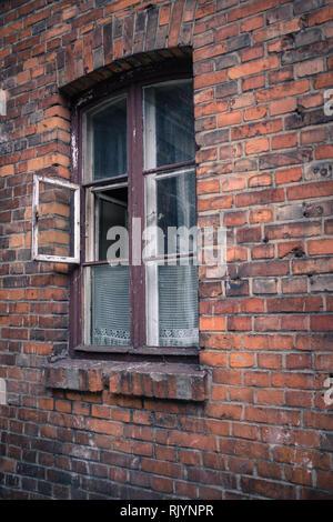 open window in rundown Eastern European brick tenement house - Stock Photo
