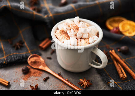 Hot cocoa drink with marshmallows in retro mug surrounded by ingredients: cinnamon, orange, anise and cove on black concrete table. Winter drink. Rust - Stock Photo