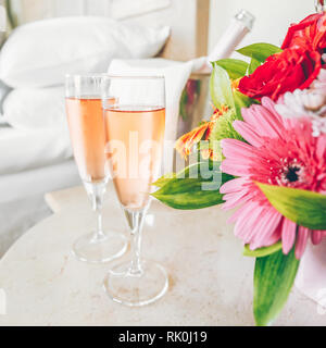 Two glasses of rose champagne in the upscale hotel room. Dating, romance, honeymoon, valentine, getaway concepts. Square. Light warm toning - Stock Photo