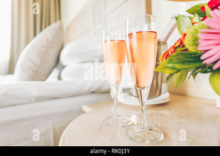 Two glasses of rose champagne in the upscale hotel room. Dating, romance, honeymoon, valentine, getaway concepts. Horizontal. Light warm toning - Stock Photo