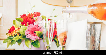 Pouring champagne into glasses in the upscale hotel room. Dating, romance, honeymoon, valentine, getaway concepts. Horizontal, banner wide screen form - Stock Photo