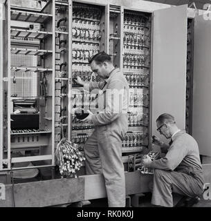 1950s, male technicians working in an aviation factory testing voltages with hand-held analog voltmeters or meter readers. - Stock Photo