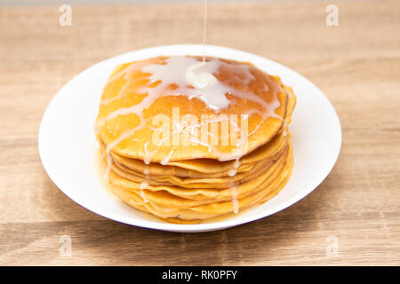 Pancakes with condensed milk on a white light background. A stack of pancakes with sweet sauce. Close up view - Stock Photo