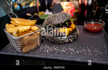 Tasty black burger, French fries in basket and ketchup served on black cutting board. Copy-space flag stuck into bun for your individual text. - Stock Photo