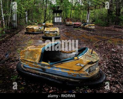Pripyat city of ghost and playground abadoned cars. famous playground - Stock Photo