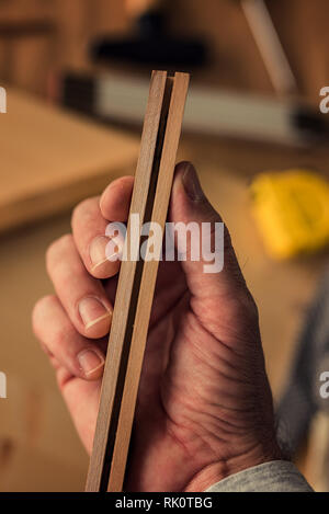 Carpenter examining picture frame wooden part, close up of hand with selective focus - Stock Photo