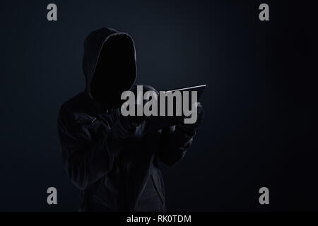 Hooded computer hacker with obscured face using digital tablet in cybercrime and cybersecurity concept, low key with selective focus - Stock Photo