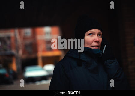 Concerned worried woman talking on mobile phone on street on cold winter day