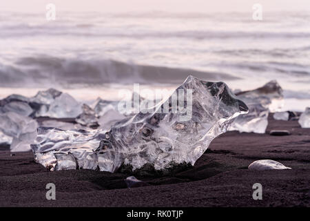 Striking ice formations on a black lava sand beach are highlighted by the evening light with red shades, narrow focus zone, depth effect, in the backg - Stock Photo