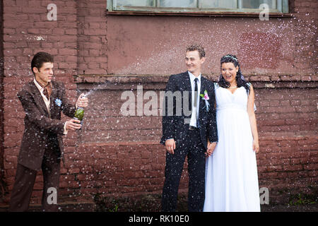 A witness at the wedding opened champagne with splashes Stock Photo