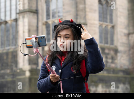 Edinburgh, UK. 8 Feb 2019. Young Chinese female tourist making funny face while taking selfie photo in Old Town of Edinburgh, Scotland, UK - Stock Photo