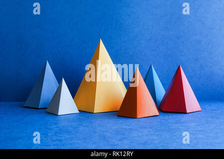 Minimal geometric still life background. Platonic solid geometric figures. Three-dimensional pyramid rectangular triangle objects on blue background - Stock Photo
