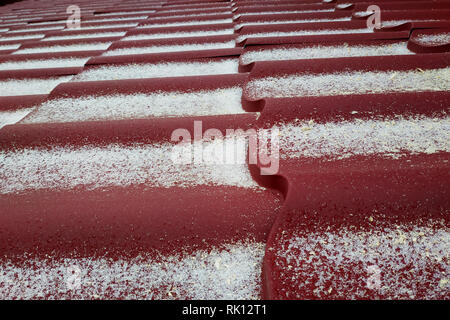 The red metal is covered with light snow 2019 - Stock Photo