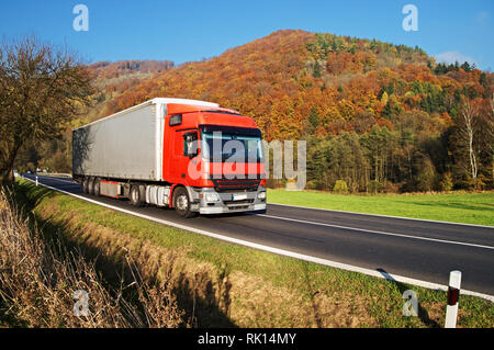 Red truck on asphalt road under forested mountain of glowing autumn colors. Clear sunny day with blue skies. - Stock Photo
