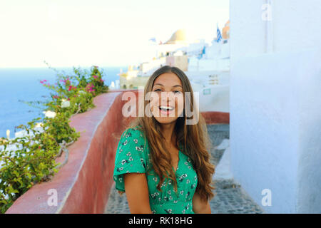 Santorini cheerful travel tourist woman visiting famous white village of Oia. Smiling tanned girl in green dress in Santorini, Cyclades, Greece. - Stock Photo