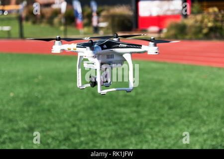 A drone is taking off from a green turf field carrying a camera - Stock Photo