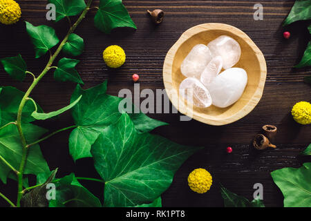 Polished Clear Quartz with Ivy and Craspedia on Dark Wood - Stock Photo
