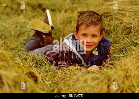 Agriculture is in my heart. Little boy relax in hayloft. Little boy enjoy free time in countryside. Go organic and natural. Bring diversity back to - Stock Photo