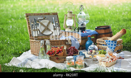 Vintage style picnic hamper with lunch in a park spread out on a rug on the grass with cheese, fresh fruit, bonbons, pickles bread and red wine - Stock Photo