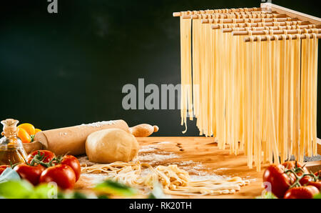 Homemade spaghetti noodles hanging up to dry with fresh ingredients for Italian cuisine on the kitchen table - Stock Photo